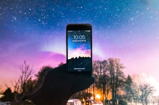 Mobiltelefon holdt opp mot farget himmel